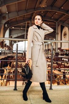 Молодая женщина в длинных сапогах и сером пальто, держащая кожаную сумочку