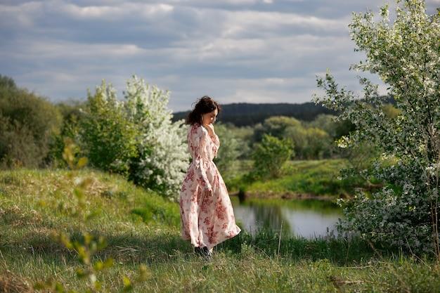 긴 드레스를 입은 젊은 여성은 호수 근처의 봄 정원에서 산책합니다. 소녀는 자연 속에서 쉬고 있다, 봄이 왔다