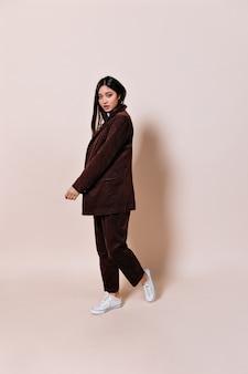 ゆったりとしたスーツを着た若い女性がベージュの壁に移動します