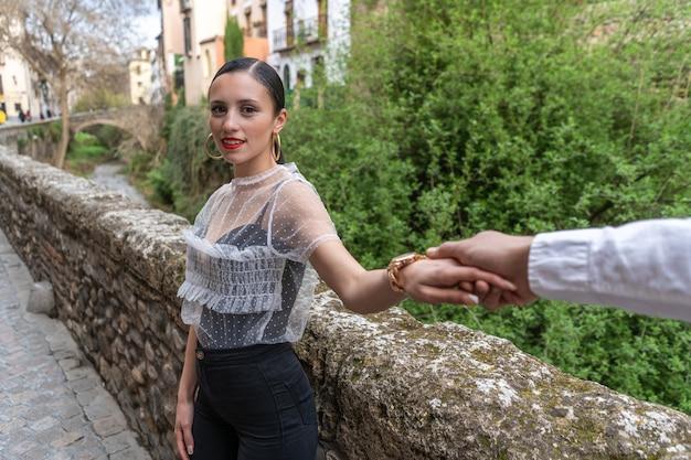 美しい環境で彼氏の手を握って恋をしている若い女性