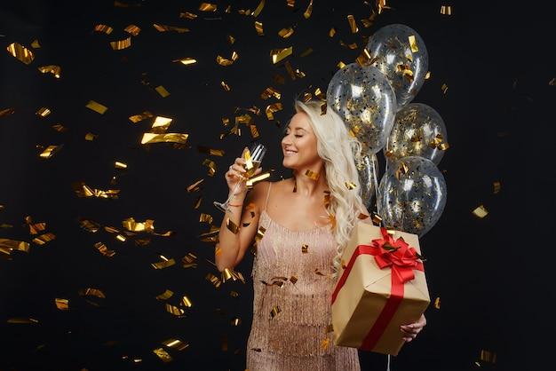 黒い壁に紙吹雪でクリスマスパーティーを祝う豪華なドレスを着た若い女性。