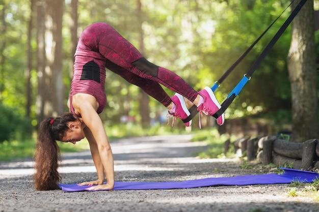 Молодая женщина в пурпурной спортивной одежде тренируется в парке, балансируя на коврике для йоги с ремнями для фитнеса, прикрепленными к дереву