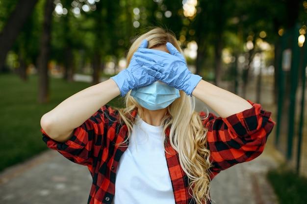 マスクと手袋の若い女性が公園で彼女の顔を覆っている