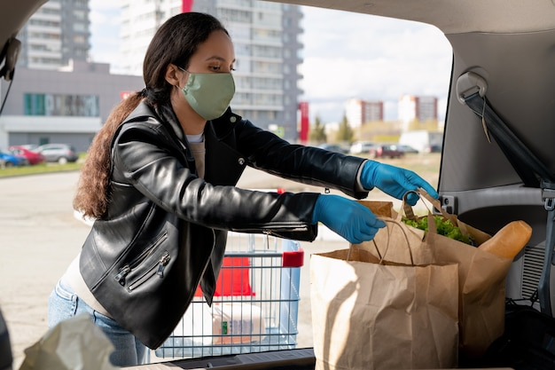 마스크와 슈퍼마켓 쇼핑 후 자동차 트렁크에 종이 가방을 넣어 장갑에 젊은 여자
