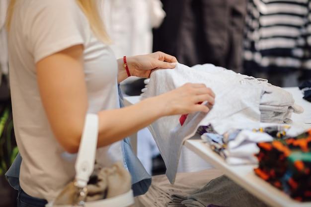 マスクの若い女性がスーパーマーケットの棚の服を選ぶ