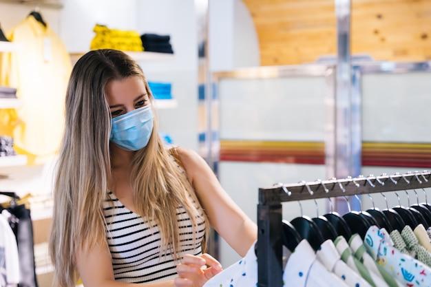 コロナウイルスのパンデミックの衣料品店でマスクショッピングの若い女性