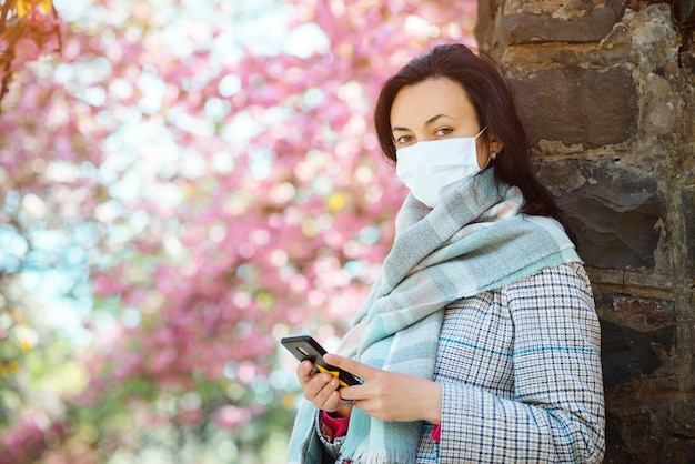 봄에 거리를 걷는 마스크에 젊은 여자. 야외에서 휴대 전화를 사용 하여 얼굴 마스크를 착용하는 여자.