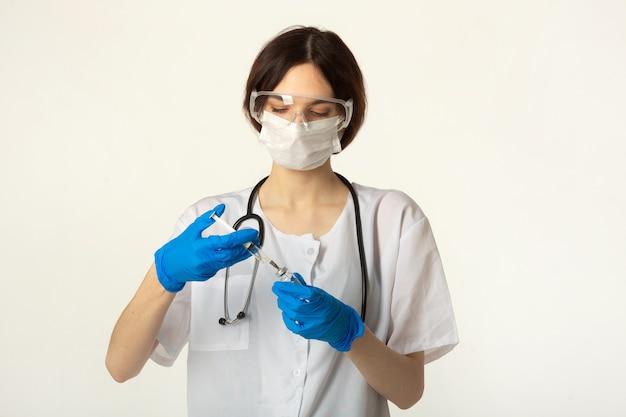 ワクチンと注射器と白い背景の上の医療服の若い女性