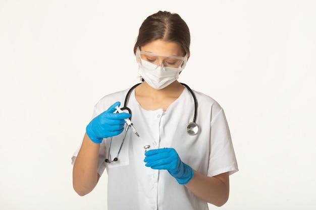 백신과 주사기와 흰색 배경에 의료 옷에 젊은 여자