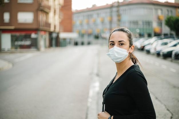 通りでコロナウイルス予防のための医療フェイスマスクの若い女性