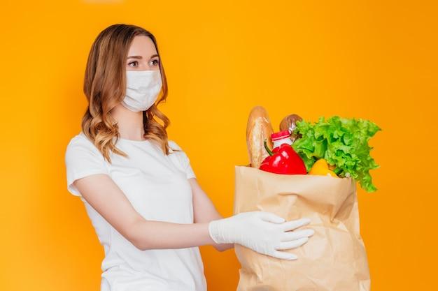 医療マスクの若い女性は、食品、果物と野菜、コショウ、バゲット、オレンジ色の壁に分離されたレタス、宅配、コロナウイルス、検疫、慈善活動の助けを借りて紙袋を保持しています。