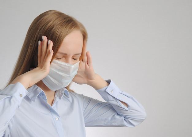 医療用マスクの若い女性は頭を抱えて痛みに苦しんでいます