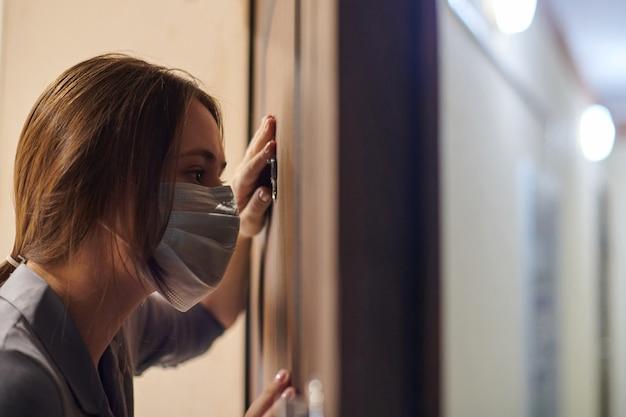 誰かがドアベルを鳴らしたときにアパートの正面玄関ののぞき穴を通して見ている医療マスクの若い女性。外出禁止令と自己隔離の概念