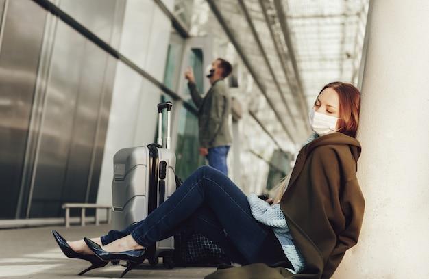 의료 마스크에 젊은 여자는 공항에서 수하물 근처에 앉는 다. 비행기로 고문당한 여자는 다음 비행기 전에 졸다. 여행 및 코로나 바이러스 개념