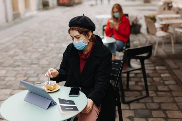 テーブルに座ってタブレット画面を見ている医療マスクの若い女性。地元のカフェテラスで屋外で自由な時間を過ごすきれいな女性。