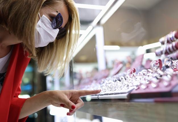 Молодая женщина в медицинской маске, солнцезащитных очках, красной куртке указывает пальцем на дисплей ювелирных изделий
