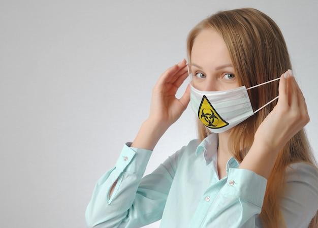 Молодая женщина в медицинской маске с печатью вирусного знака