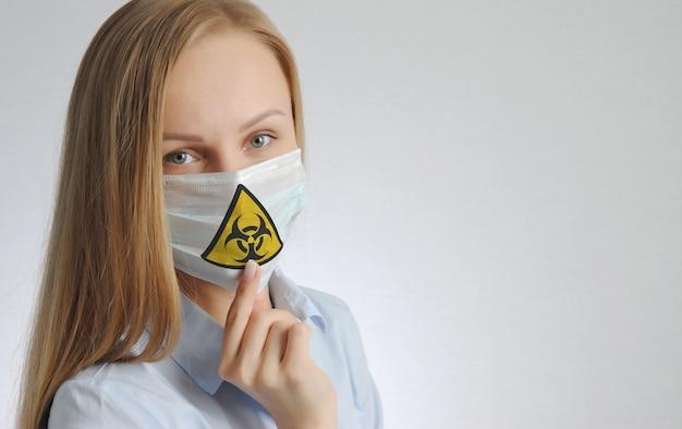 Молодая женщина в медицинской маске со знаком вируса