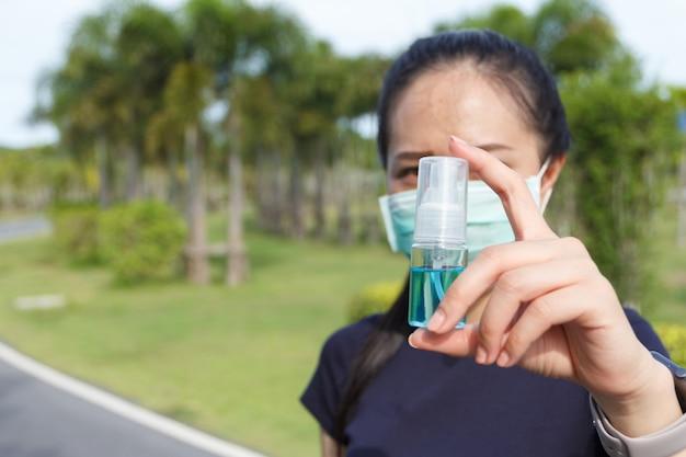 医療用保護マスクを着用し、手にアルコールを保持している若い女性。 covid19を保護するために保護マスクとアルコールを使用するキャンペーン