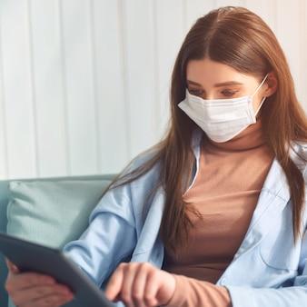 의료 보호 마스크에 젊은 여자는 침대에 태블릿을 사용합니다.