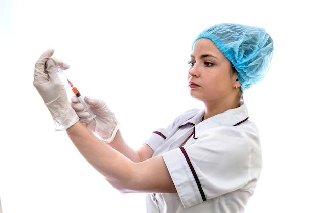 白で隔離の注射器と医療制服の若い女性