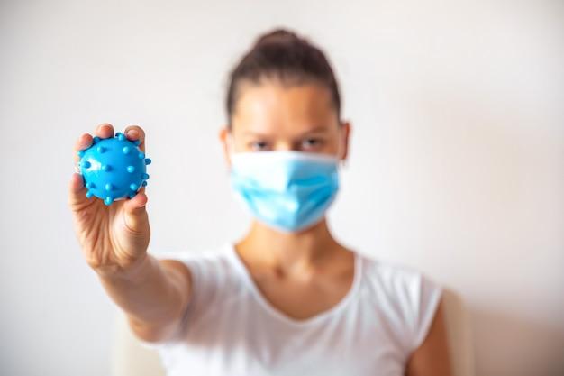 白い背景、医療概念、停止コロナウイルスcovid-19概念の手にウイルスとして青いプラスチックボールと薬のマスクの若い女性