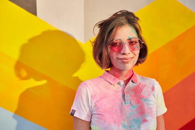 トレンディなサングラスをかけている乱雑なホーリーパウダーの若い女性