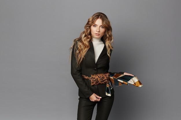 灰色の背景でポーズをとって、孤立したヒョウベルトバッグとモダンなスーツの若い女性。フォーマルな服とヒョウ柄の流行のベルトバッグで美しいモデルの女の子。オフィシャルファッション