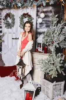 Молодая женщина в модном зимнем наряде позирует в интерьере, оформленном на новый год