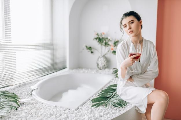 N白いバスローブ、バスルームのインテリアの若い女性