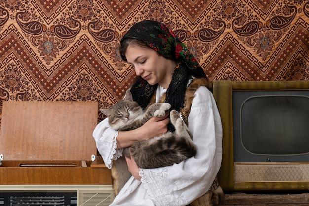 国立の若い女性が高齢者のレトロな部屋の中で座っていると彼女の手で猫を保持して閉じます