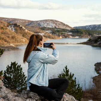Молодая женщина на природе фотографирует
