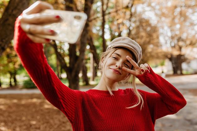 素敵な赤いプルオーバーの若い女性が公園の小道で自分撮りをします。