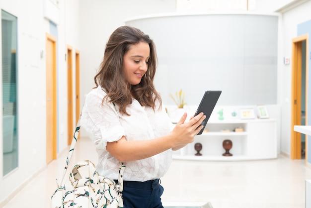 Молодая женщина в офисе, глядя на планшет