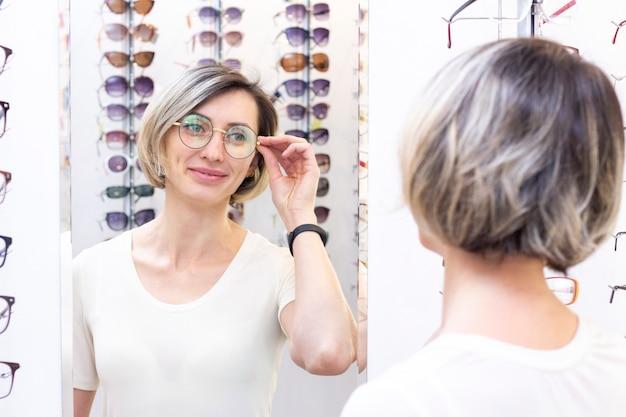 眼鏡店で眼鏡店で新しい眼鏡を選ぶ若い女性。光学の店の眼鏡。女性は眼鏡を選びます。感情。眼科。