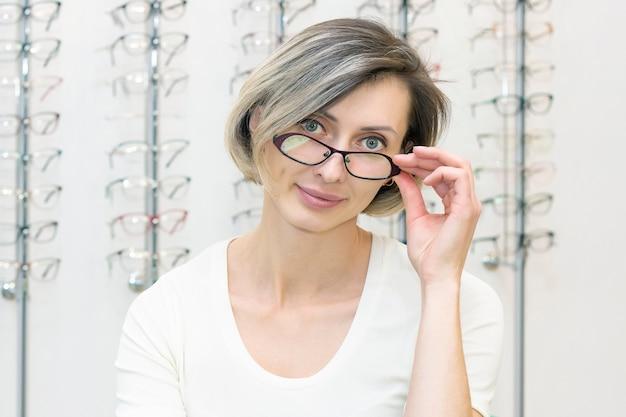 Молодая женщина в магазине оптики, выбирая новые очки с оптиком. очки в магазине оптики. женщина выбирает очки. эмоции. офтальмология.