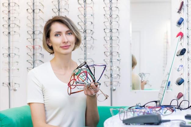 眼鏡店で眼鏡店で新しい眼鏡を選ぶ若い女性。光学の店の眼鏡。女性は眼鏡を選びます。手にたくさんのグラス。眼科。