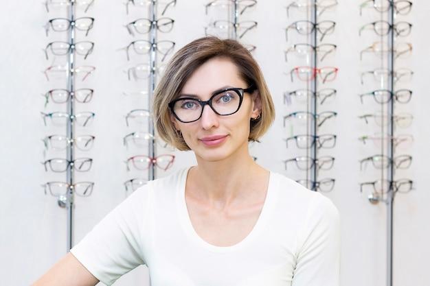 眼鏡店で眼鏡店で新しい眼鏡を選ぶ若い女性。光学の店の眼鏡
