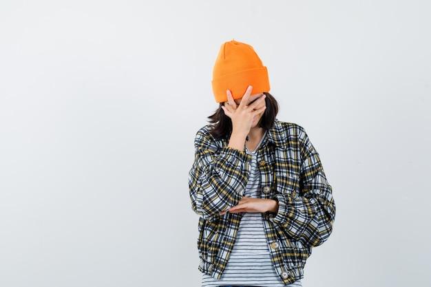オレンジ色の帽子と市松模様のシャツの若い女性が幸せそうに見える手で頭を傾ける
