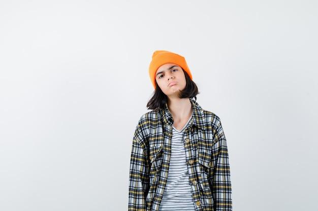 オレンジ色の帽子の市松模様のシャツを着た若い女性が苦しんでいるように見える下唇を曲げる