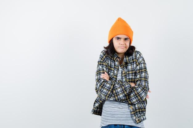腕を組んで立っているオレンジ色の帽子の市松模様のシャツの若い女性