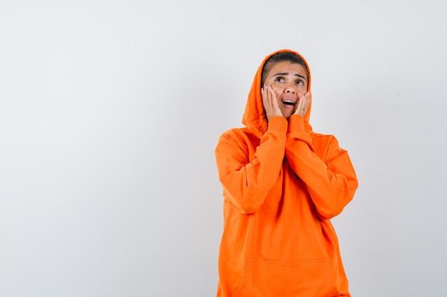 オレンジ色のパーカーを着た若い女性が誰かを呼んで集中しているように口の近くで手を握っている