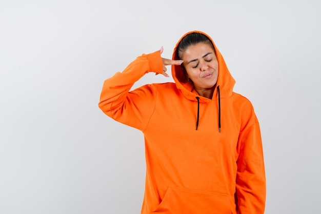 人差し指で自分を指して真剣に見えるオレンジ色のパーカーの若い女性