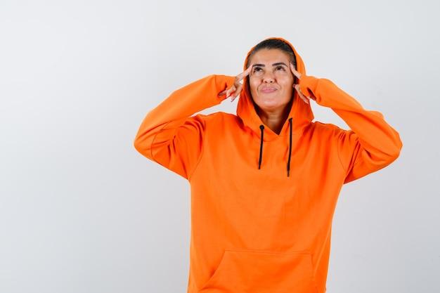 オレンジ色のパーカーの若い女性がこめかみに指を置き、上を見て、何かについて考え、物思いにふける