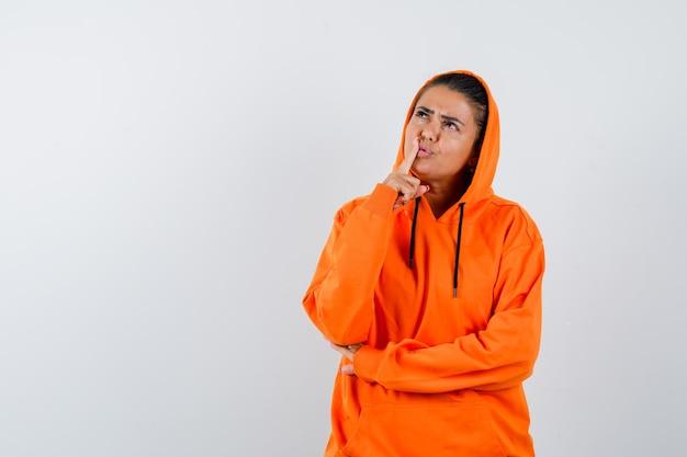 沈黙のジェスチャーを示し、真剣に見えるオレンジ色のパーカーの若い女性