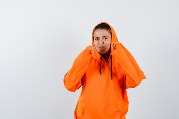 권투 선수 포즈에 서 있고 아름 다운 찾고 오렌지 까마귀에 젊은 여자