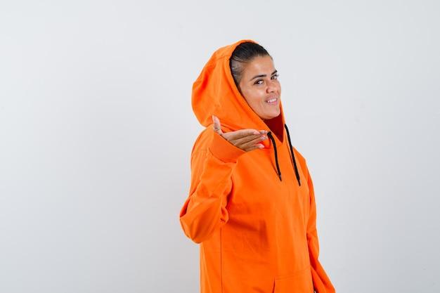 Молодая женщина в оранжевой толстовке с капюшоном протягивает руку к камере и выглядит счастливой