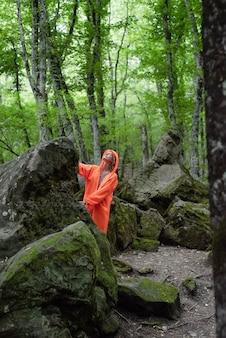 緑の森でハイキングオレンジ色のレインコートの若い女性。アクティブなライフスタイルと旅行