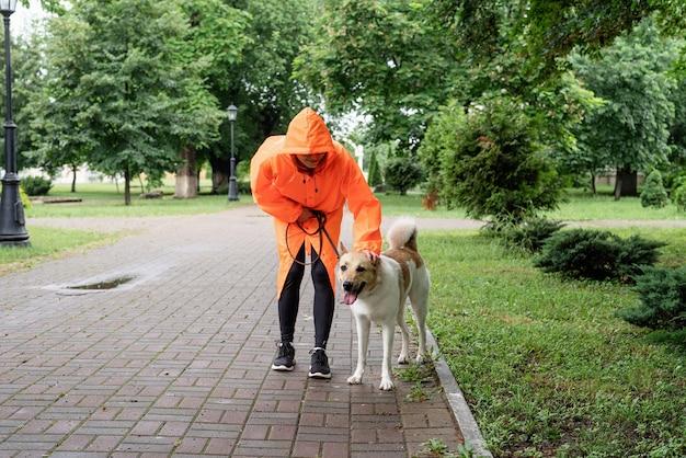 공원에서 강아지와 함께 산책하는 주황색 비옷을 입은 젊은 여성