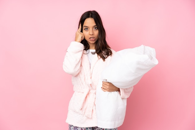 Молодая женщина в пижаме, изолированные на розовом фоне, думает об идее